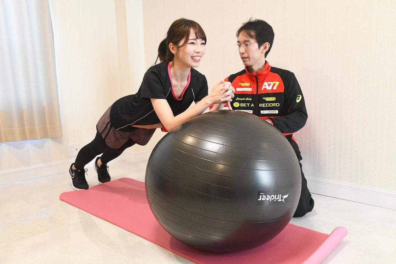 女性がバランスボールを使用して男性トレーナーからパーソナルトレーニングを受けている写真