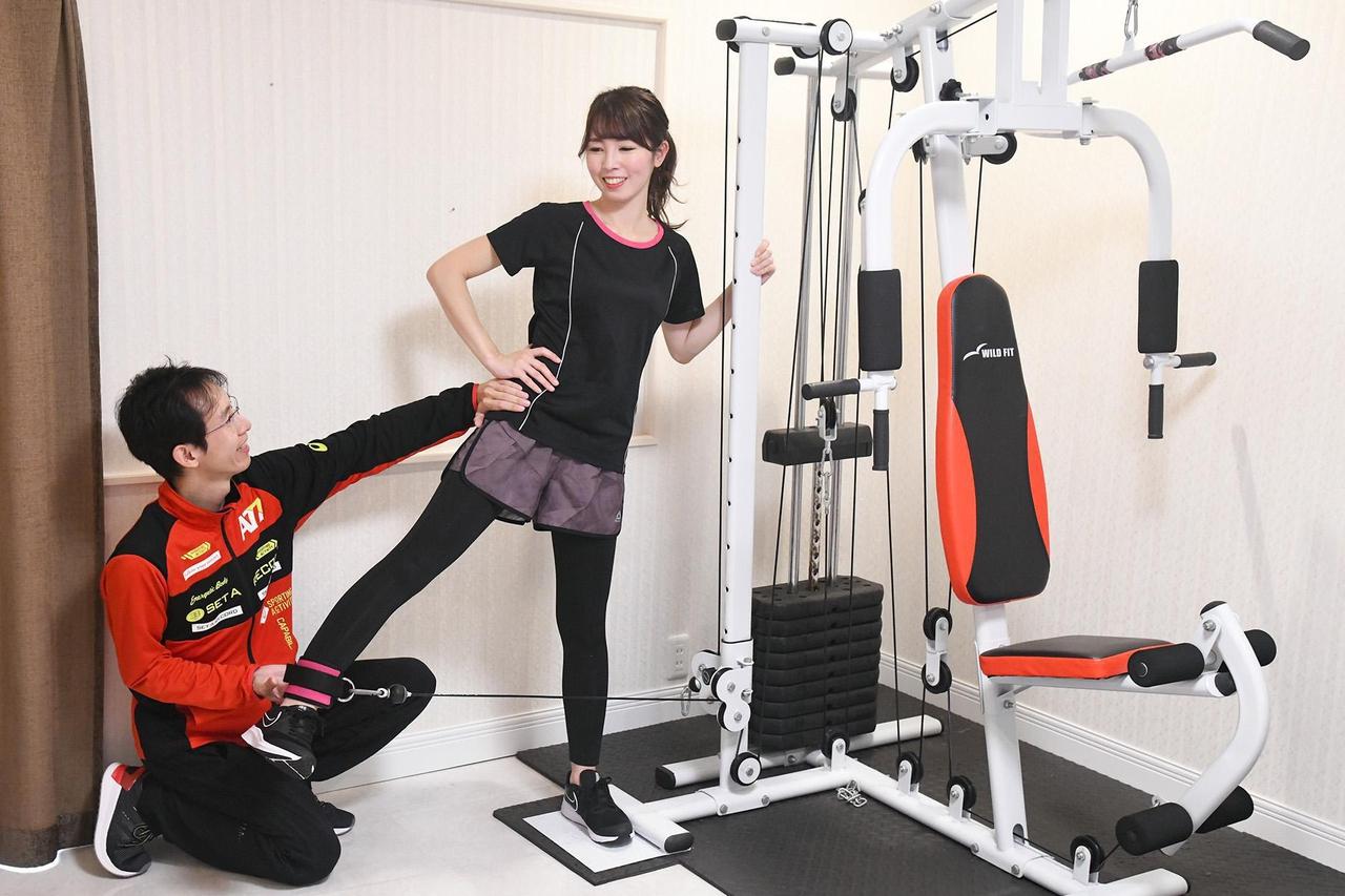 女性がトレーニングマシーンを利用して脚の筋力アップを図る写真