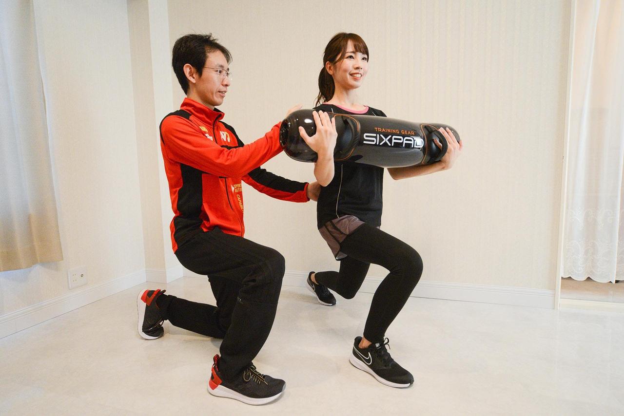 女性が筋力と体幹を鍛える器具を使用して男性トレーナーからパーソナルトレーニングを受けている写真