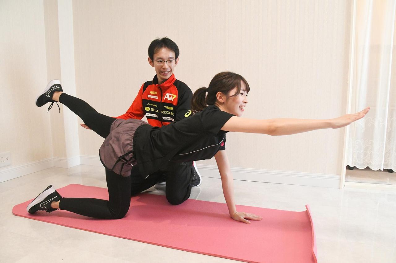 女性が男性トレーナーよりパーソナルトレーニングを受けている写真