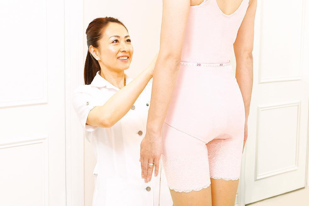 女性スタッフが女性のお腹周りの採寸をしている写真