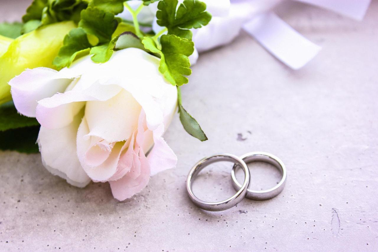 ブートニアのそばで結婚指輪が重なっている写真
