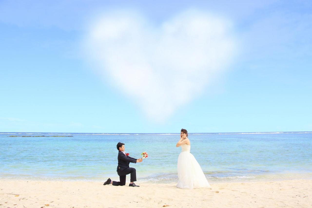 海辺で跪いてプロポーズをしている写真