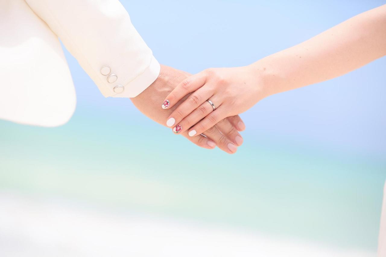 海辺でウエディングドレスとタキシードを着た男女が手を繋いでいる写真
